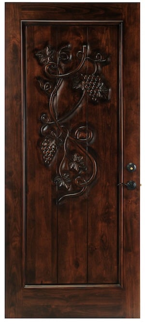 A solid wood door with a hand carved grapevine design.