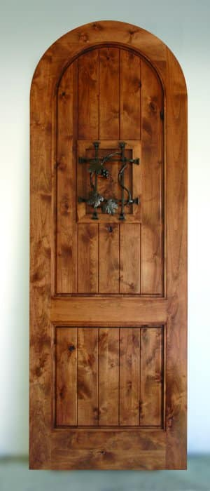 A solid wood door with a false speakeasy door. Grapevine design wrought iron. Arched top.