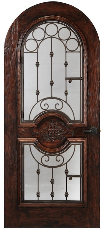An arched door with operable wrought iron design with a hand carved grape design in the center. One of our most eye-catching designs.