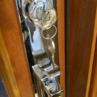 Vantage handle set in polished chrome in custom wine cellar door in Frisco Texas home wine cellar under staircase.