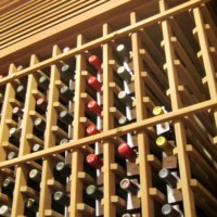 Wood wine racks offer Individual wine bottle storage to Frisco, Texas homeowners in their under-the-staircase wine room.