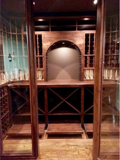 Looking through doorway of custom wine cellar at rolling case storage.