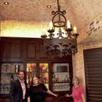 Matt Helm and Nancy Higgins standing with a friend in this Dallas Wine Cellar. A custom wine cellar and a tasting room can really make a house more of a home now while increasing your home\'s resale value in the future.