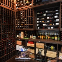 The finished custom wine room, complete with counter and table for wine tasting. Incredible storage and displays were also built with wood to the client\'s specific  needs.